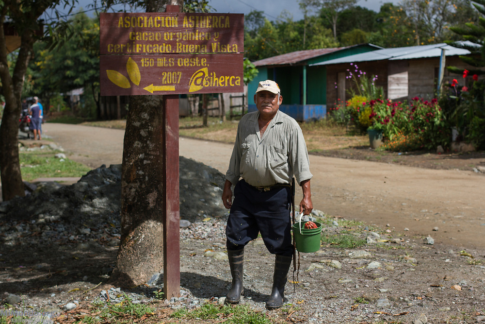 Mercedes Díaz Jaime, 63, local cacao producer and president of ASIHERCA, stands next to the association's sign in the village of Buena Vista. ASIHERCA (Asociación de Iniciativas y Hermanamientos de El Castillo), a local association of small-scale producers, exports cacao certified by the Fairtrade Labeling Organization (FLO). Buena Vista, El Castillo, Río San Juan, Nicaragua. January 27, 2014.