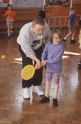 Games teacher teaching junior school pupil how to hit ball with tennis racket,