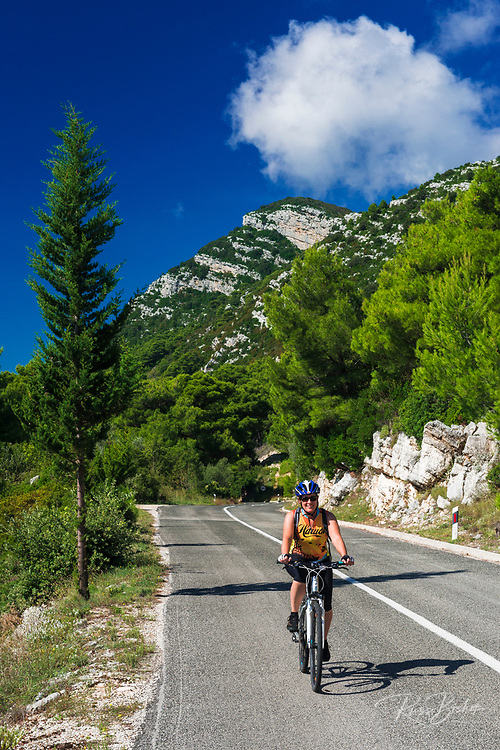 Cyclist on the road into Sobra, Mljet Island, Croatia