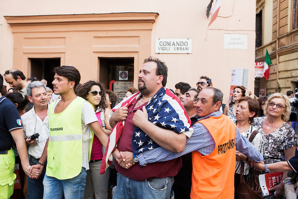 SANT'AGATA DE GOTI, ITALY - 23 JULY 2014: Franco, an Italian American who has lived in Staten Island for 20 years before returning to his home town, wears an American flag on his shoulders behind security guards next to the city hall as he waits for Mayor of New York Bill de Blasio to step out, in Sant'Agata de Goti, Italy, on July 23rd 2014.<br /> <br /> New York City Mayor Bill de Blasio arrived in Italy with his family Sunday morning for an 8-day summer vacation that includes meetings with government officials and sightseeing in his ancestral homeland.