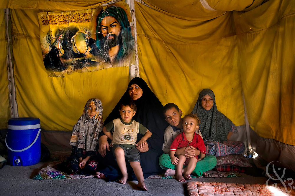 An Iraqi woman sits with her children and their friends under a Shia religious poster inside their tent at the al-Manathera IDP camp located 20 kilometers south of the Iraqi city of An-Najaf September 20, 2007. Opened in February for 10-15 families, the camp now has swollen to 230 mostly Shia families displaced by sectarian violence in Baghdad, Falluja, and Diyala province. The families living here are dependent now on the aid of the Iraqi Red Crescent and the UNHCR.