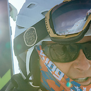 Scott McGee hikes to the top of Powder 8 Face with Cody Peak reflected in his goggles.