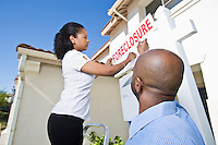Couple putting up notice outside house