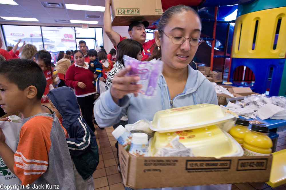 27 NOVEMBER 2008 -- PHOENIX, AZ: People pick up their free breakfasts at a McDonald's in Phoenix, AZ, Thanksgiving day. The McDonald's restaurant, in an economically disadvantaged section of Phoenix, has been serving free breakfasts on Thanksgiving for 15 years. Thousands of people stand in line for hours for pancakes, milk and orange juice. This year, more than 3,000 people came to the breakfast. Arizona Governor Janet Napolitano was the featured guest. Photo by Jack Kurtz / ZUMA Press