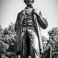 "Chicago Lincoln standing statue in black and white. The Abraham Lincoln statue is located in Lincoln Park and is named ""The Man"" and is also referred to as Standing Lincoln."