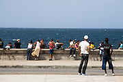 People hang out by the malecon in Havana, Cuba on Saturday June 28, 2008.