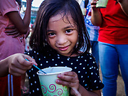 "26 JANUARY 2017 - MALILIPOT, ALBAY, PHILIPPINES: A girl who lives on the slopes of the Mayon volcano eats a ""champorado,"" a Filipino sweet of sticky rice, coconut milk and chocolate, provided by the Philippine Red Cross in the shelter in Malilipot. The volcano was relatively quiet Friday, but the number of evacuees swelled to nearly 80,000 as people left the side of  the volcano in search of safety. There are nearly 12,000 evacuees in Santo Domingo, one of the communities most impacted by the volcano. The number of evacuees is impacting the availability of shelter space. The Philippines is now preparing to house the volcano evacuees for up to three months.    PHOTO BY JACK KURTZ"