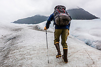 A mountain guide walking on the Mendenhall Glacier, Juneau, Alaska USA.