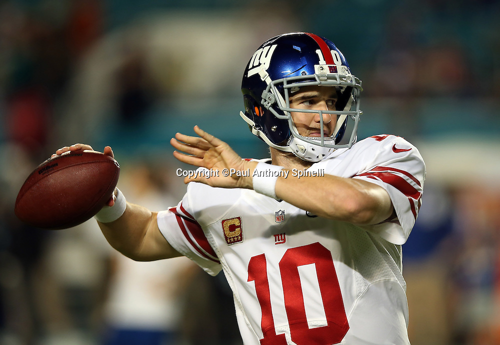 New York Giants quarterback Eli Manning (10) throws a pass as he warms up before the NFL week 14 regular season football game against the Miami Dolphins on Monday, Dec. 14, 2015 in Miami Gardens, Fla. The Giants won the game 31-24. (©Paul Anthony Spinelli)