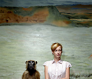 20 something female standing next to guinea baboon taxidermy looking away.