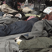 Terminal 3 at Piraeus port in Athens is a scene of scores of refugees with little more than a blanket each. This square of material is what each one has to sleep, sit, eat, living on. In the facility there is no water to shower and many families, children, individuals have been in the space for weeks in these conditions.