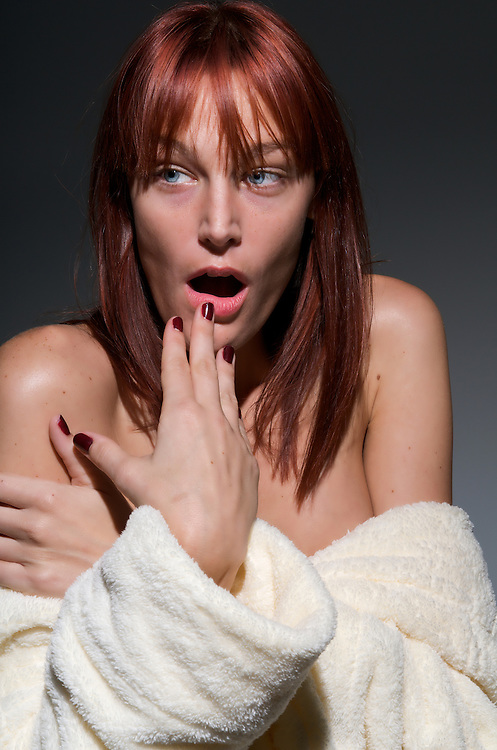An young red-hair woman is taken by surprise after taking a shower.