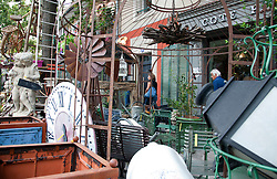 Two unidentied shoppers view the sidewalk offerings of the Cote Parc shop, one of the most unusual of the more than 300 antique shops and decorators for which the town of L'Isle-sur-la-Sorgue is famous.