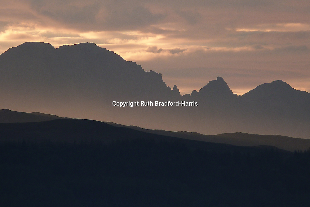 The awe-inspiring pinnacled outline of the Bla Bheinn (Blaven) massif seen in silhouette across the Sleat peninsula, Isle of Skye from Mallaig at sunset. Evening mist is rising below the peaks. Amazingly, this image was taken at approaching midnight on Midsummer's Day.<br /> <br /> Date taken 24 June 2016.