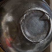 Play of light on stainless steel mesh colander strainer basket use in kitchen for straining and draning  salad or pasta.