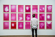 Uranium (Pink) - Alibis a Sigmar Polke retrospective at the Tate Modern – he was viewed as one of the most experimental artists of recent times and the exhibition covers his full career, bringing together works from around the world in a huge variety of materials. Highlights include: Girlfriends – An iconic early Pop painting from 1965 of a bikini-clad girl; Potato House – Standing over 6 feet tall, this sculpture of a house is made from wooden lattices covered in real potatoes; Mao – A huge felt banner covered in scraps of cloth and painted with an image of Chairman Mao; Watchtowers – A series of neon-coloured paintings incorporating silver, resin, fabric and bubble-wrap; and other paintings made from such diverse materials as meteorite dust, soot, lead, coal, elastic bands and medical tape. The exhibition runs from 9 October 2014 – 8 February 2015.  Tate Modern, Bankside, London, UK 07 Oct 2014.