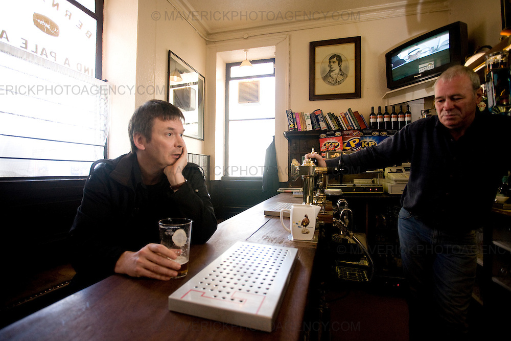 Ian Rankin, Scottish author and creator of the Inspector Rebus novels drinks a beer at the 'Oxford Bar' with the barman. The bar was made famous as it is the place where character Inspector Rebus drinks..Picture Michael Hughes/Maverick