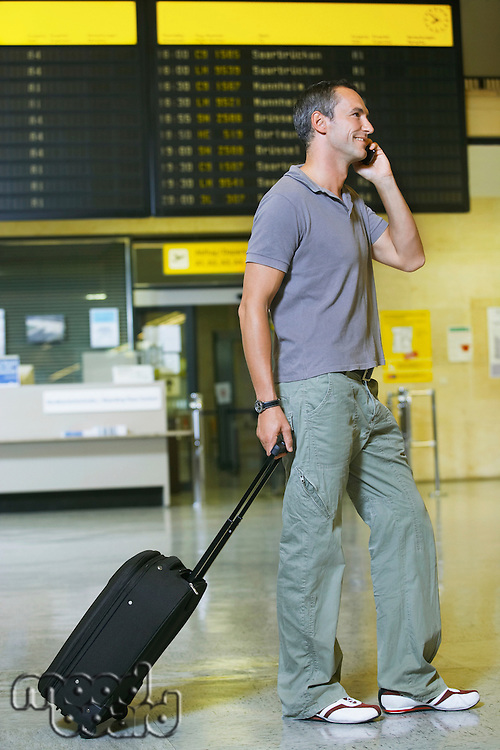 Traveller using mobile phone in front of flight status board in airport