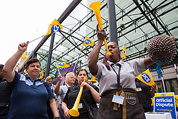 London, UK. 15 July, 2019. Ana Joaquim (r) sounds a vuvuzela among catering and cleaning staff belonging to the PCS trade union and outsourced to work at the Department for Business, Energy and Industrial Strategy (BEIS) via contractors ISS World and Aramark standing on the picket line outside the Government department after walking out on an indefinite strike for the London Living Wage, terms and conditions comparable to the civil servants they work alongside and an end to outsourcing.