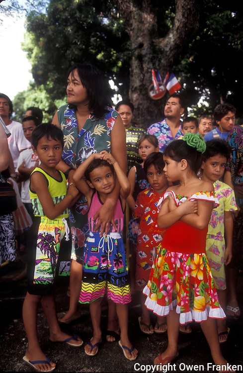French Polynesia, Islands in the South Pacific, part of the French overseas Territories..Tahiti..Photograph by Owen Franken..Tahiti - families waiting for Bastille Day parade