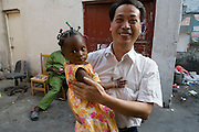 24 October 2007 - Guangzhou, China - A Chinese manager plays with a customer's child. The manager works for Guillaume Akochaye from Benin, a shipping agent who has a registered company in Guangzhou called the Richland Trade Ltd, with offices in China and Benin. He has been in China for many years and speaks Chinese fluently. By some estimates over 10,000 Africans from many different nations live and pass through Guangzhou which has overtaken Hong Kong as the new hub for African businessmen looking to cut out the middle man. Some come for a few weeks, others years. These African traders, most of whom come from West African nations like Ghana, Togo and Nigeria, profit by purchasing cheap goods direct from Chinese factories and then sending them back to their home countries where they can be sold at higher prices. Photo Credit: Luke Duggleby