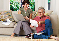 Middle-aged couple looking at bill and laptop