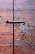 Nicely preserved old wood door with ancient locking mechanism and hardware.
