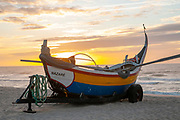 Traditional colorful Portuguese fishing boat on the beach at Vieira de Leiria. A Portuguese village and also a parish in the municipality of Marinha Grande, Portugal at sunset