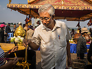 25 FEBRUARY 2015 - PHNOM PENH, CAMBODIA: A man lights incense at a Buddhist shrine in Phnom Penh.     PHOTO BY JACK KURTZ