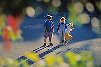 Three young kids ages 4, 6, 7 play hopscotch on a quiet street on an autumn day in Whistler, BC Canada.