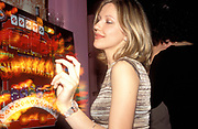A girl dancing by a fruit machine, in a bar, UK 2004