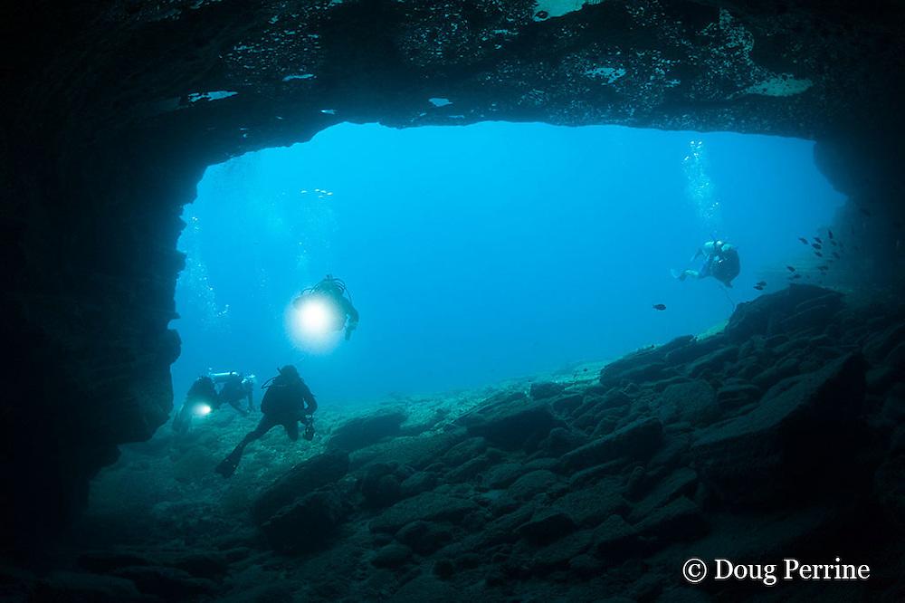 divers swim into cavern at Niihau Arches dive site between Lehua Rock and Niihau Island, Hawaii, USA ( Central Pacific Ocean )