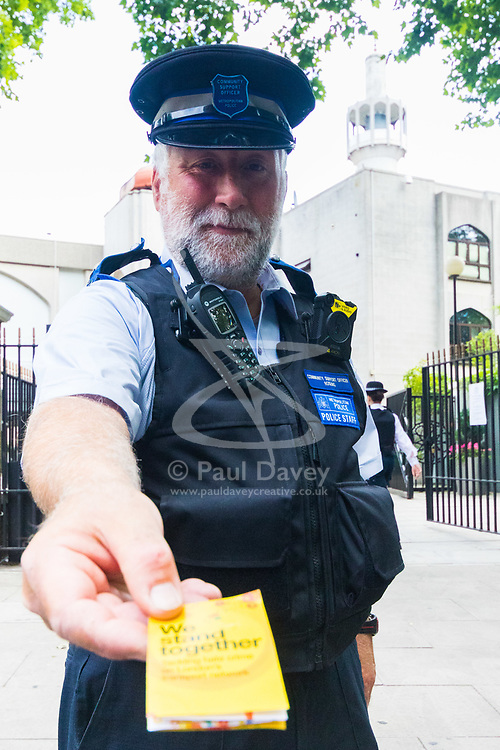 London, June 23rd 2017. Police are in evidence as Muslim worshippers gather for Friday Prayers at London Central Mosque in Regents Park, following the suspected terror attack in the early Hours of Monday June 19th when Darren Osbourne, 47, from Cardiff, now charged with terrorism-related murder, is alleged to have run down a group of Muslims in Finsbury Park. A Police Community Support Officer offers a leaflet on tackling hate crime on London's transport network.