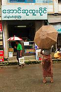 Men wearing longyi at the streets of downtown Yangon during rainfall