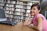 Female university student with laptop in library