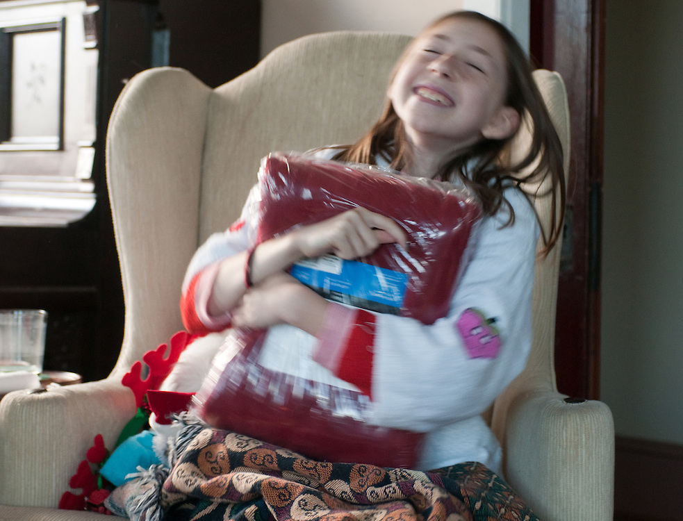 Young girl opening gift on Christmas morning