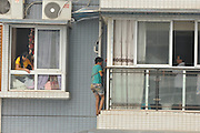 YIBIN, CHINA - SEPTEMBER 08: (CHINA OUT) <br /> <br /> Schoolboy Climbs Out Of Window To Avoid Violence<br /> <br /> 12-year-old Xiao Kai prepares to come inside after sitting out a window of his 11th floor apartment on September 8, 2014 in Yibin, Sichuan Province of China. Xiao Kai climbed out of the window to avoid his mother''s violence as he didn't finish his homework on time. Xiao Kai came inside after being persuaded by his family members and police officers for two hours. Xiao Kai's mother said several times that she will pursue the matter no further. <br /> ©Exclusivepix