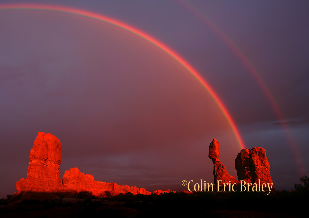 A passing storm brings a double rainbow in Arches National Park as the rock formation known as Balanced Rock glows from the setting sun. Colin Braley/Wild West Stock