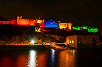 Amber Fort & Palace illuminated at night during a sound and light show (with Maota Lake in foreground), Amber, near Jaipur, Rajasthan, India.