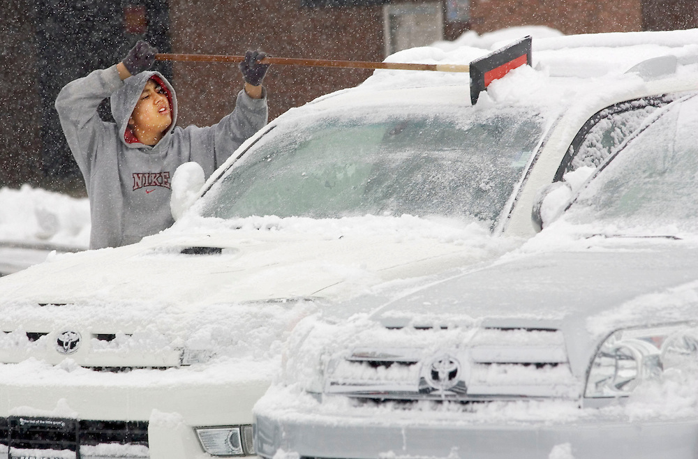 Manuel Arredondo of Bountiful scraps the snow off of cars and trucks at the Menlove Dodge Toyota car dealership Jan. 6, 2005 in Bountiful, Utah. Workers said they were barely able to keep up with the snow on Thursday morning.  Photo by August Miller