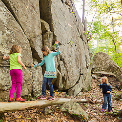 Kids attempt to traverse a log next to a cliff in the forest at the Kenyon Hill preserve in South Berwick, Maine.