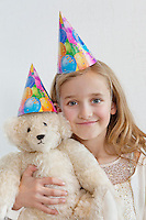 Portrait of a happy young girl wearing party hat with soft toy over colored background