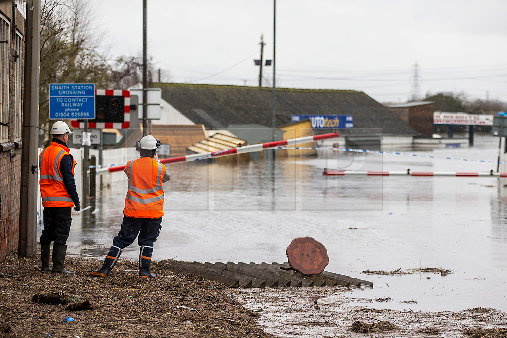 © Licensed to London News Pictures. 28/02/2020. Snaith UK. Two men asses damage to a flooded rail crossing in Snaith where residents have been evacuated from flood water in Yorkshire as the UK prepares for storm Jorge. Photo credit: Andrew McCaren/LNP