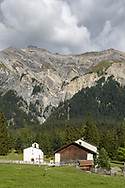 The chapel Sankt Cassian and historic farm buildings in Lenz with the Lenzerhorn and the Piz Linard, Parc Ela, Grisons, Switzerland