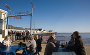 People sitting at cafe tables on a sunny winter day at Southwold pier, Suffolk, England