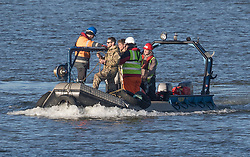 © Licensed to London News Pictures. 12/02/2018. London, UK. A member of the Royal Navy Bomb Disposal Team arrives by boat near London City Airport which remains closed after a World War II era bomb was found in The River Thames during routine work on nearby King V Dock. Police have evacuated nearby residents, closed the airport and set up a 214-metre exclusion zone. Photo credit: Peter Macdiarmid/LNP