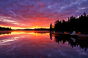 Reflection of clouds in Lac du Fou at sunrise with canoes<br />
