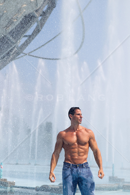 muscular bodybuilder in an outdoor fountain