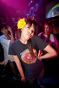 ASIAN GIRL WITH YELLOW FLOWER IN HER HAIR POUTING IN A CLUB