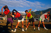 Wearing numbered bibs, four Nepali boys warm-up before an army exercise trial known as the British Fitness Test (BFT) at the British Gurkha Regiment's army camp at Pokhara, Nepal. These boys are among those trying for a highly-valued place in the regiment after a gruelling series of tests to eliminate the weaker and less able candidates. 60,000 boys aged between 17-22 (or 25 for those educated enough to become clerks or communications specialists) report to designated recruiting stations in the hills each November, most living from altitudes ranging from 4,000-12,000 feet. After initial selection, 7,000 are accepted for further tests from which 700 are sent down here to Pokhara in the shadow of the Himalayas. Only 160 of the best boys succeed in the journey to the UK. Nepal has been supplying youth for the British army since the Indian Mutiny of 1857.